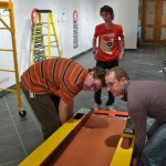 Roger Hill, Matthew Callinan, and Michael Rushmore position a skee-ball machine